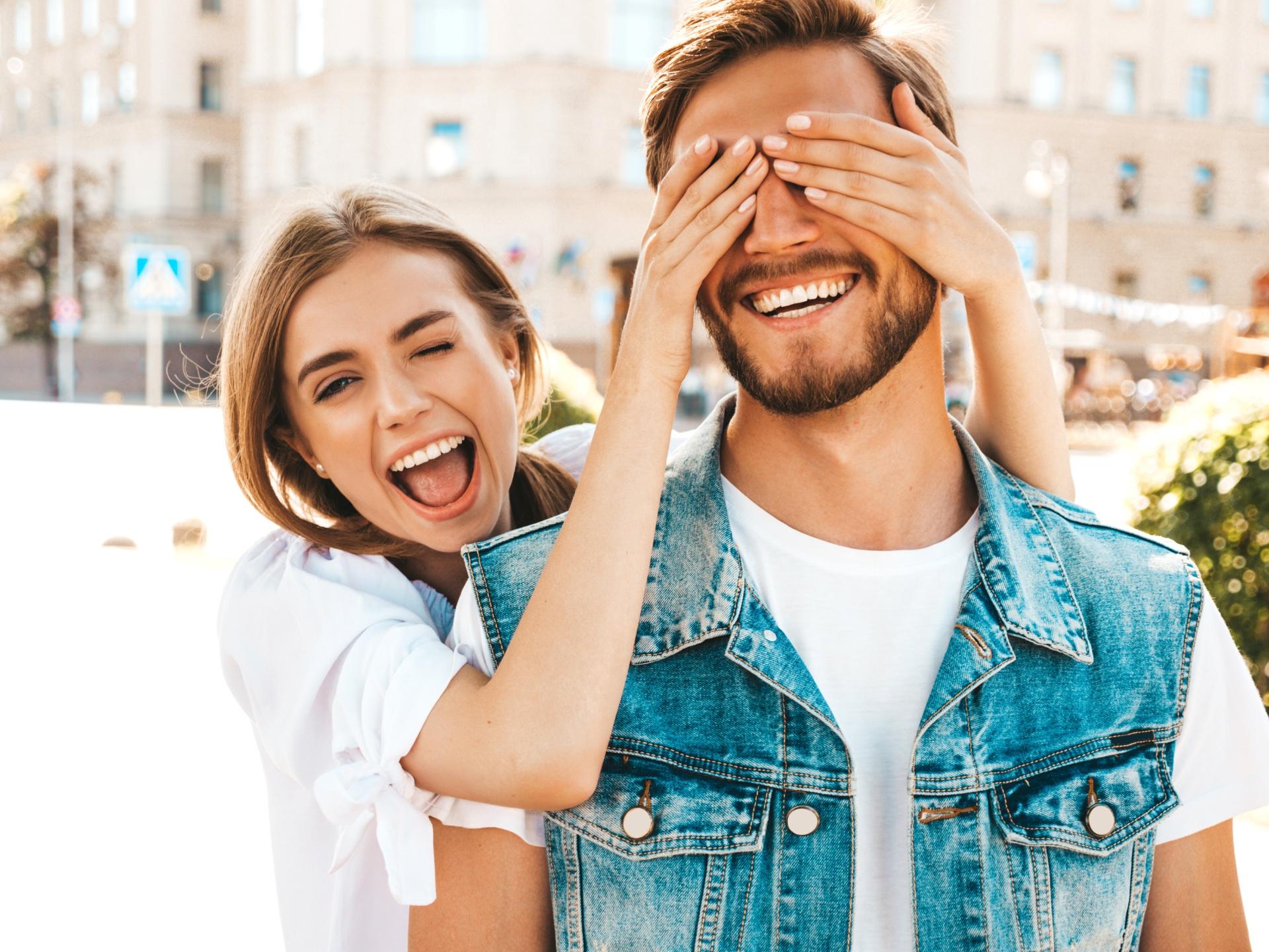 Усмихнати мъж и жена с бели зъби на улицата